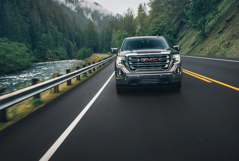 A dark metallic gray colored GMC sierra cruising down a forest road, facing the camera.