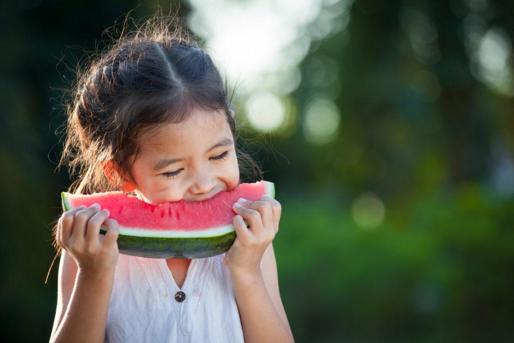 Little girl eating a slice of watermelon outside