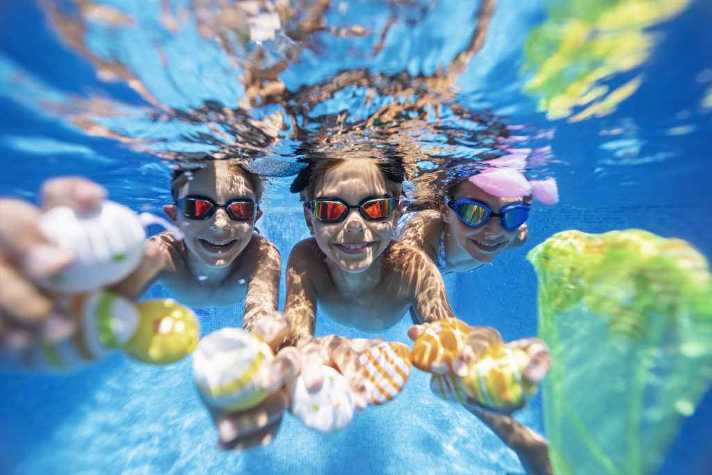 Kids wearing goggles underwater in a pool