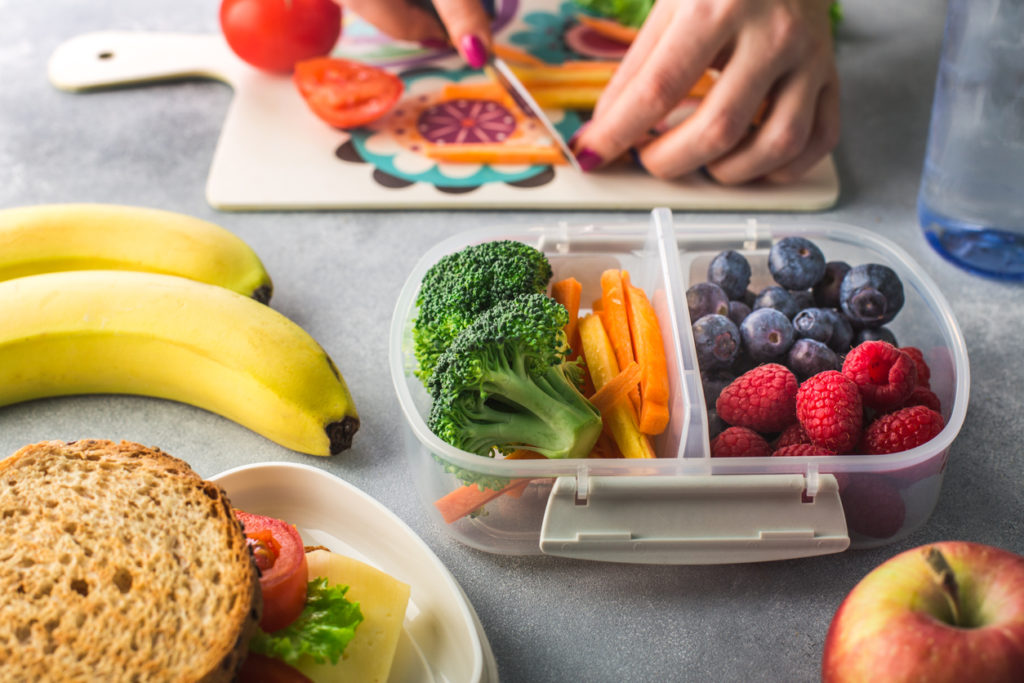 Mother giving healthy lunch for school