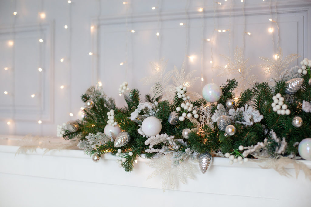 fireplace is decorated with white and silver balls, bells, cones and Christmas tree wreath.