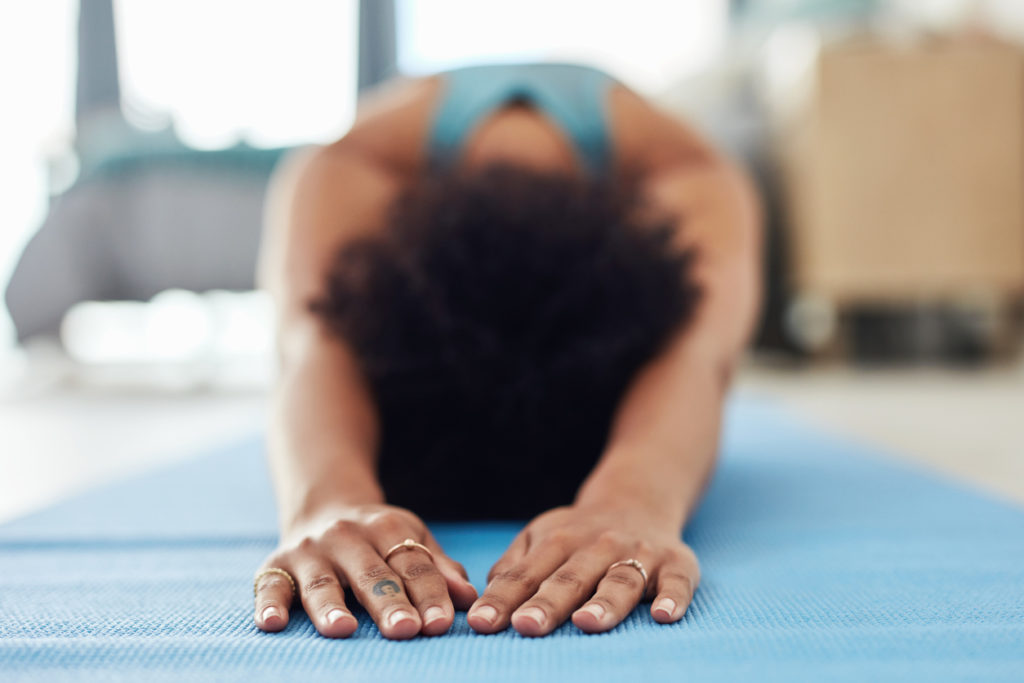 Shot of a fit young woman doing yoga at home