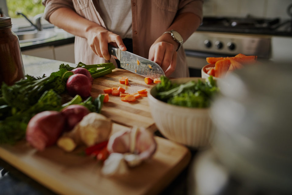 Female hands cutting vegetables on cutting board