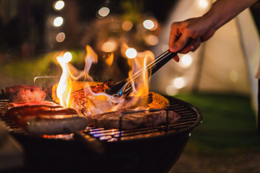 flames rising from grill at night
