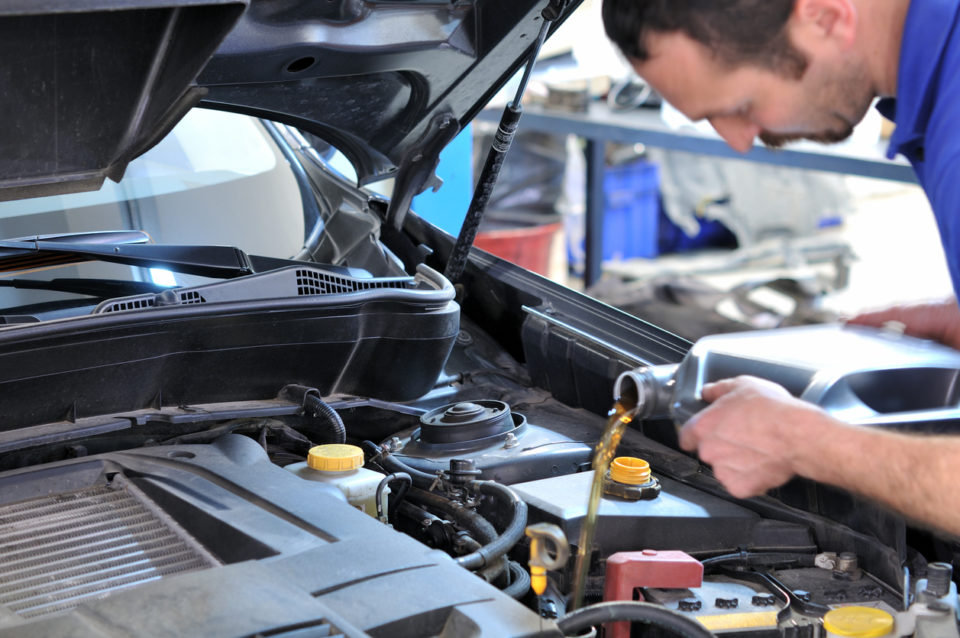 Mechanic changing oil in vehicle