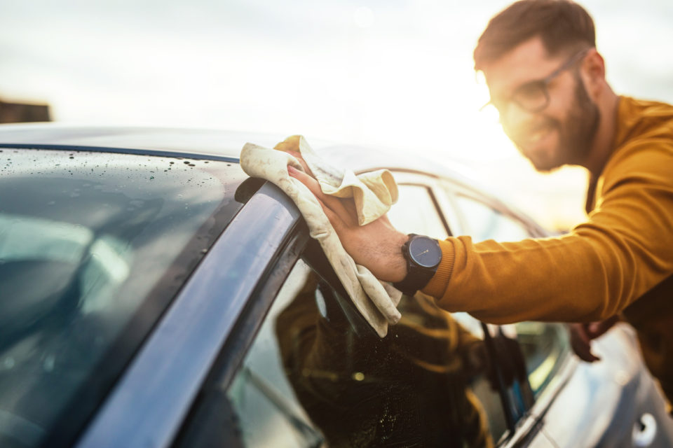Shot of a happy young man cleaning his car with microfiber cloth on a sunny day.