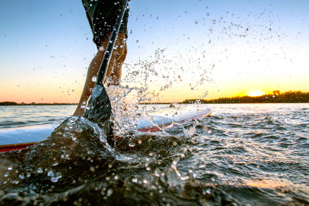 Close up of a Paddle-boarder in action during the sunset