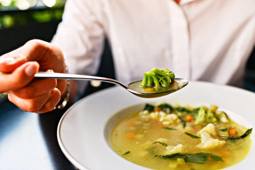 Woman Eating Vegetable Soup