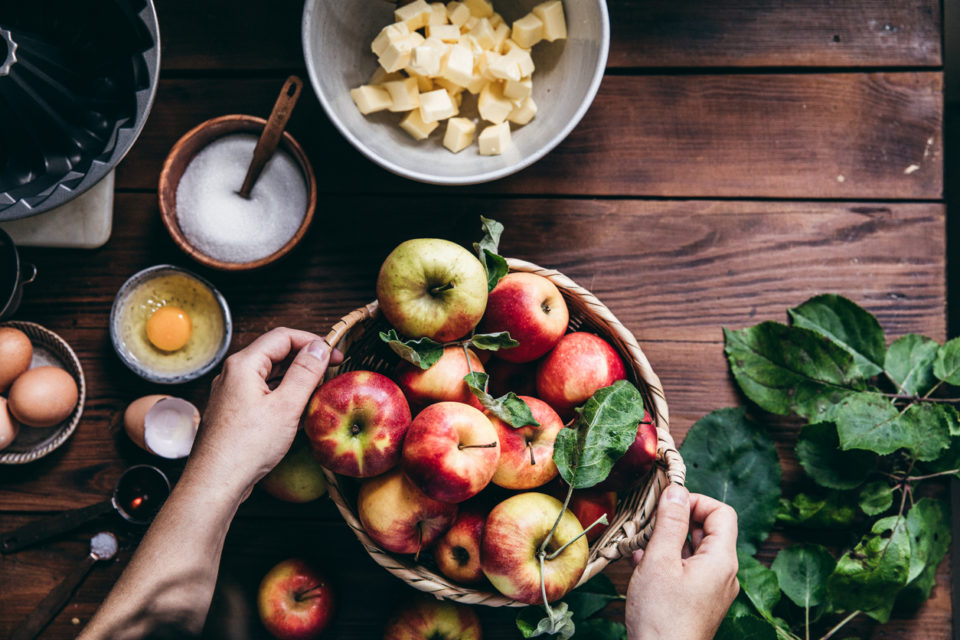 Woman baking cake with freshly picked apples