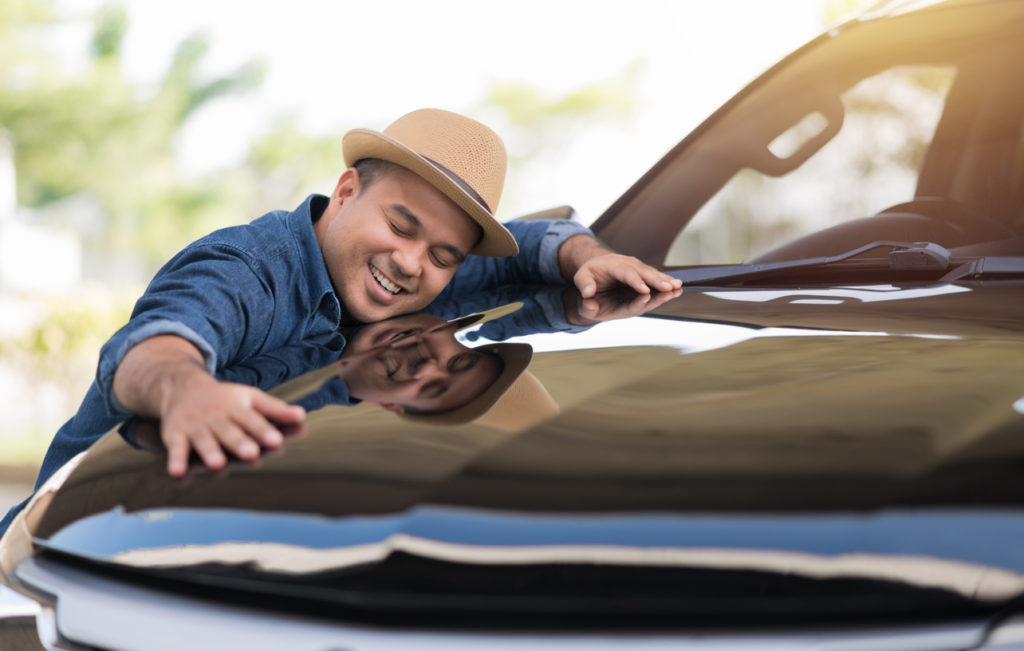 young man hugging car exterior